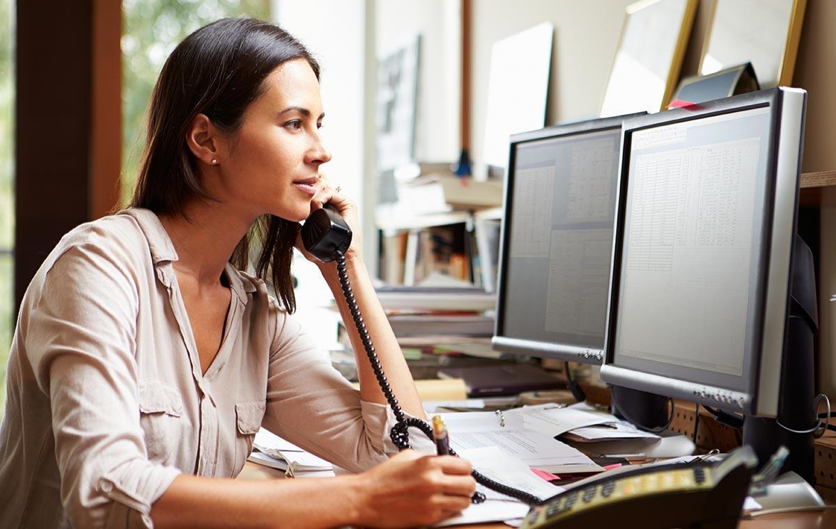 Woman talking on desk phone