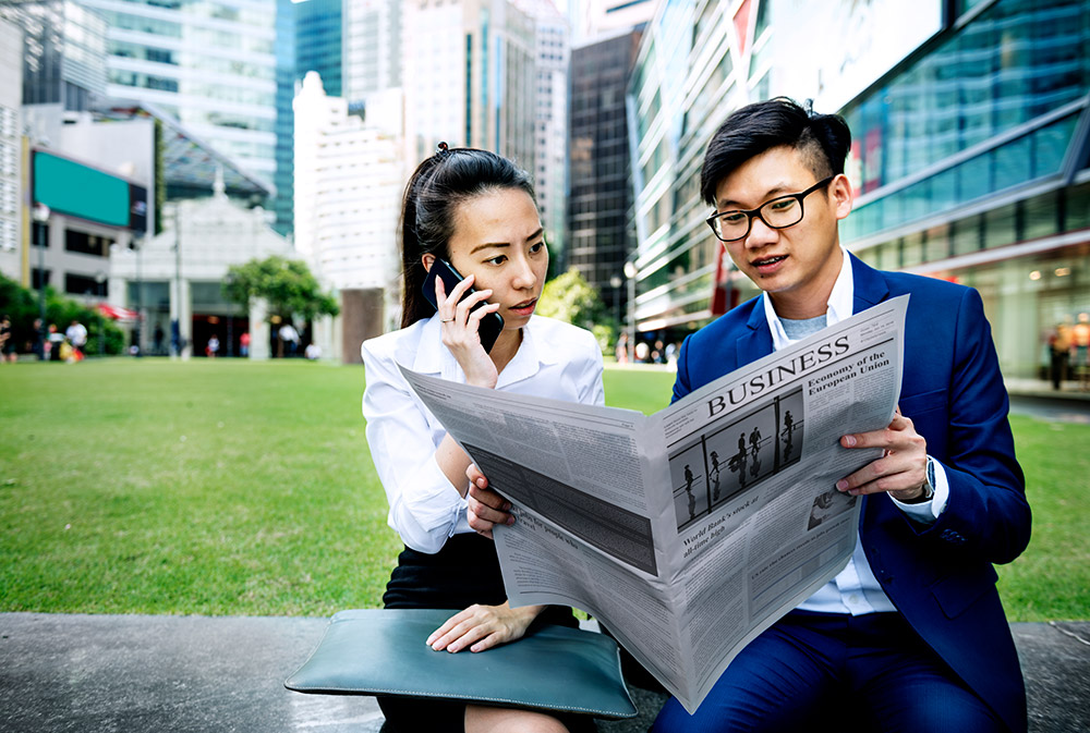Young professionals reading business news