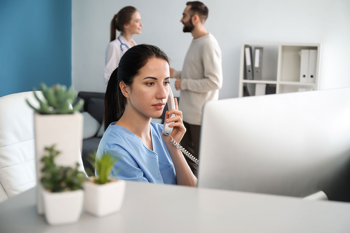 Female medical receptionist on phone will colleagues talking in background